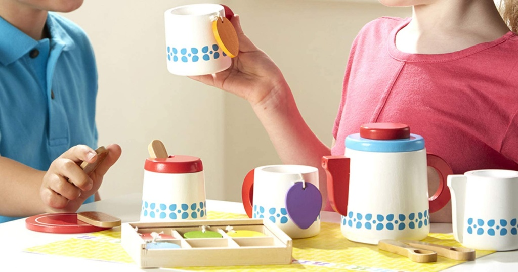 two children playing with a wooden melissa & doug tea set