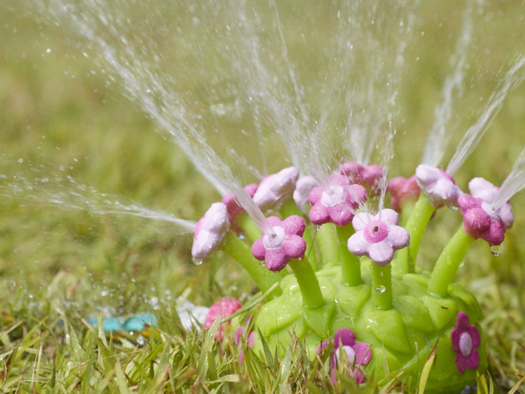 pink and green plastic sprinkler spouting water and sitting in the grass