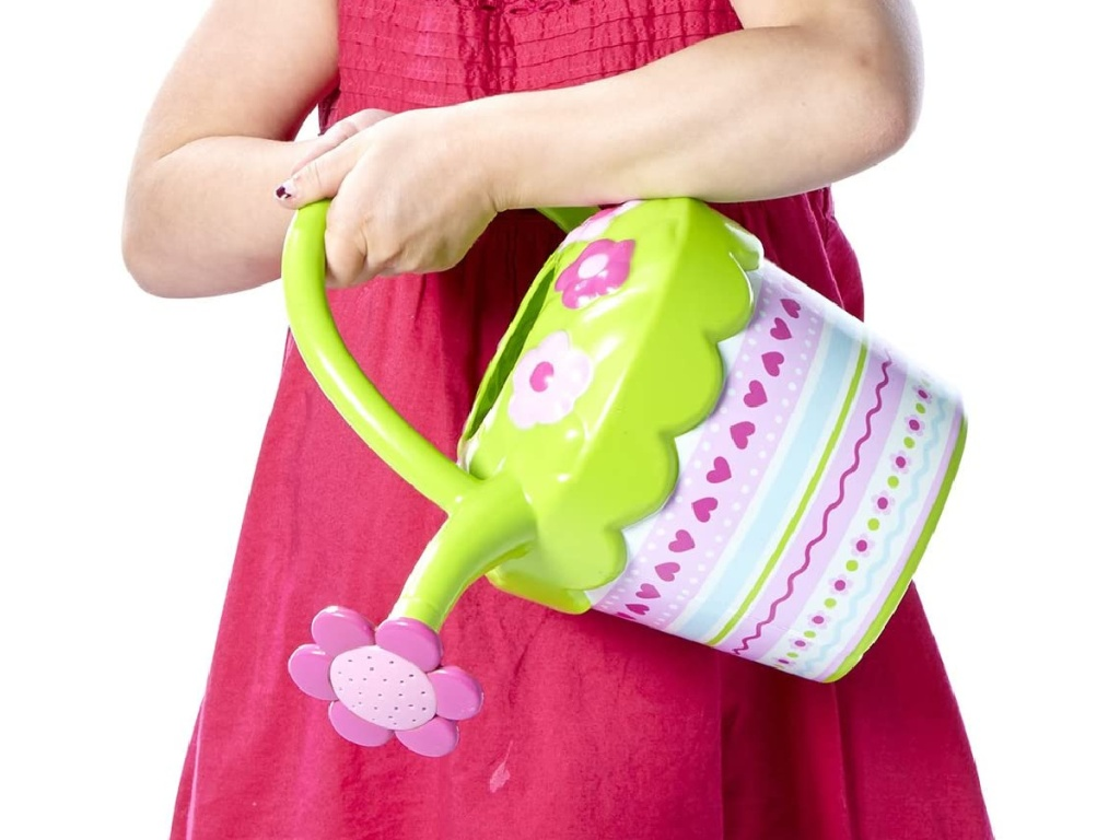 little girls wearing a bright pink dress holding a pink and green plastic watering can