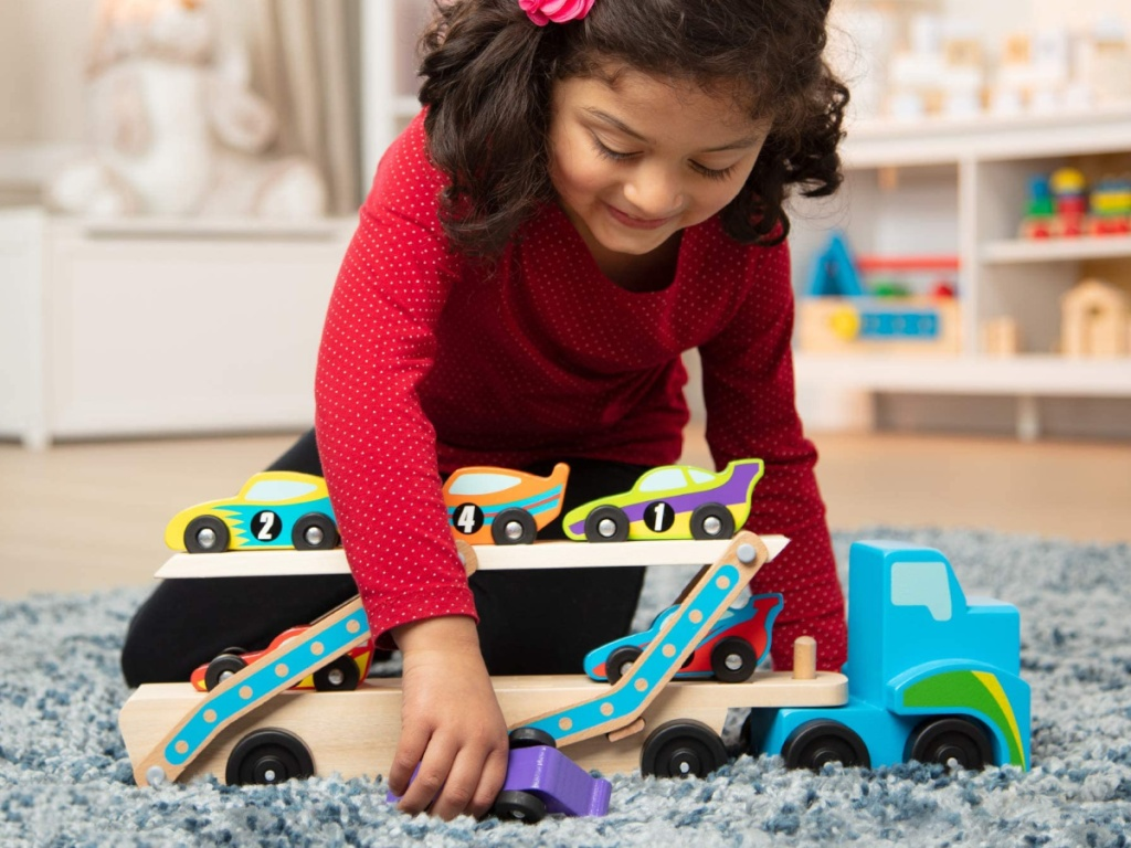 little girl kneeling on the floor playing with a wooden car carrier toy