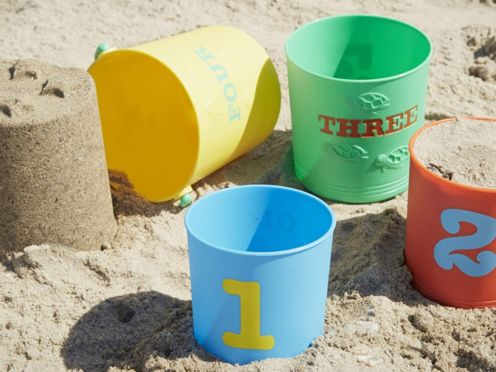 multi colored sand buckets numbered and sitting on a beach