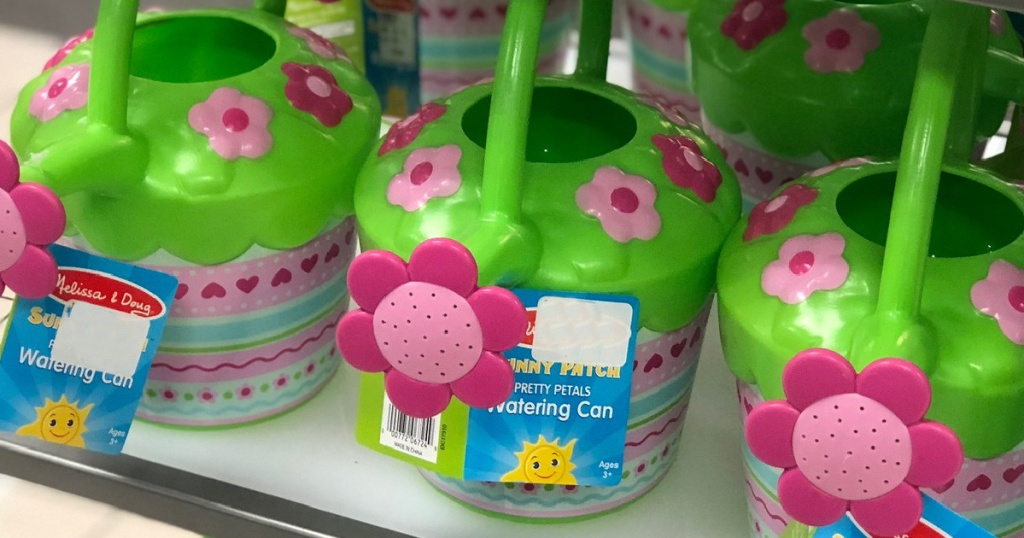 3 Melissa and Doug Pretty Petals Watering Cans sitting on a store shelf