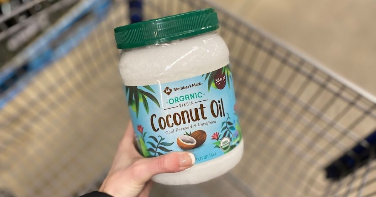 hand holding a jar of coconut oil
