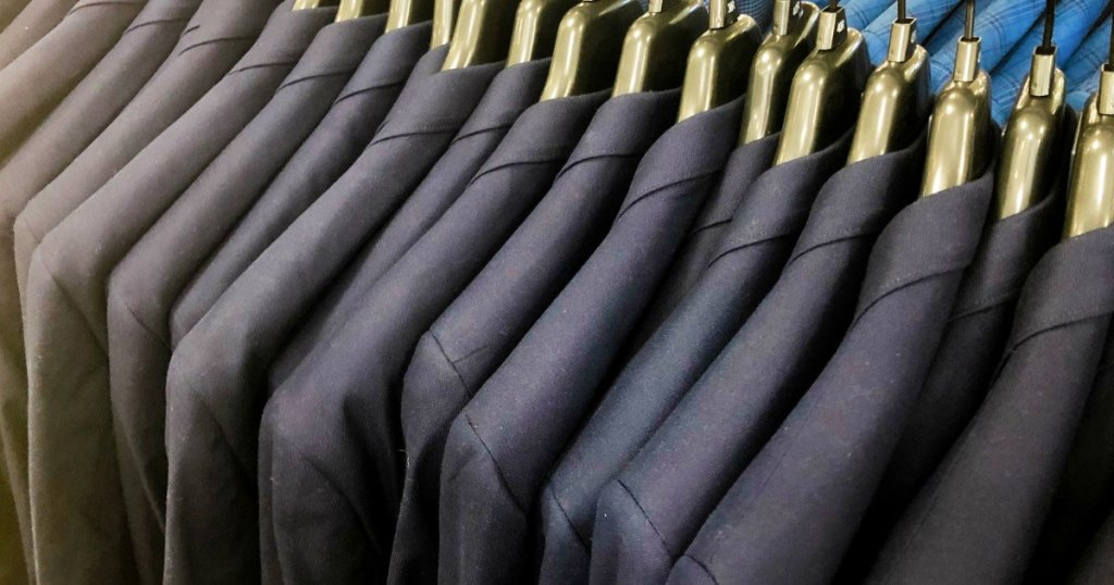 various shades of men's suits on gold hangers