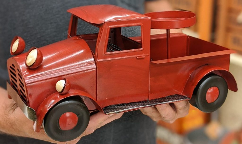 man holding red truck candle holder