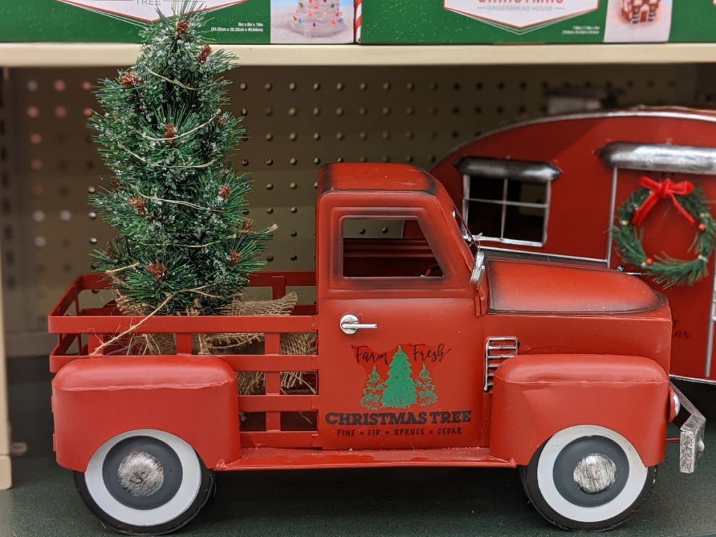 red truck with light up Christmas tree in bed decor on store shelf