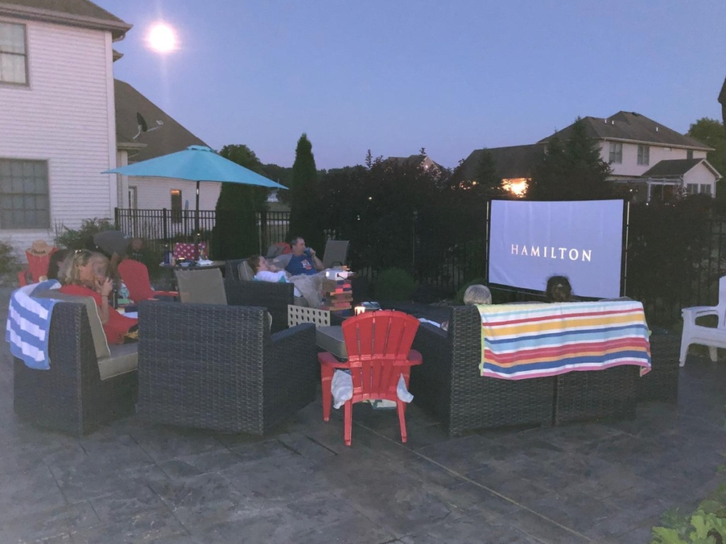 family sitting outside on a patio watching a movie play on a big screen