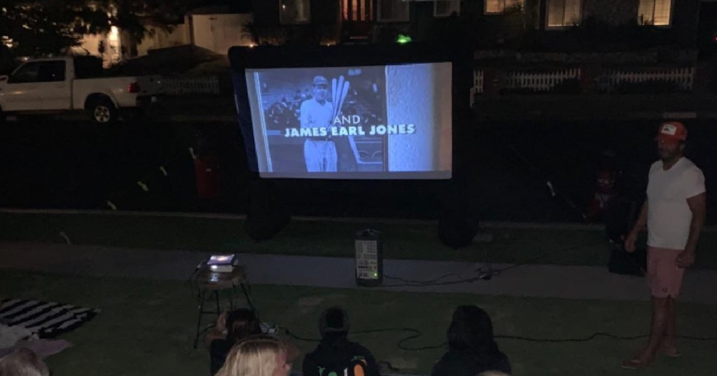 mini projector showing a film outside on a large white screen at dusk