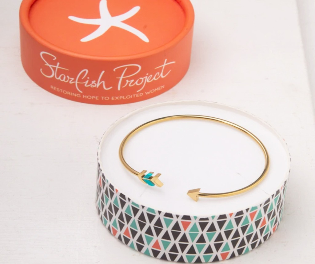 gold arrow shaped cuff bracelet in round box with orange lid in background that says Starfish Project on it