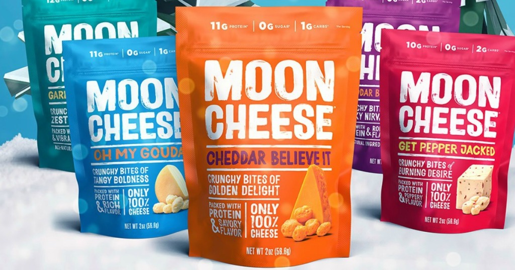 Large bags on Moon Cheese in a variety of flavors on a Christmas themed background