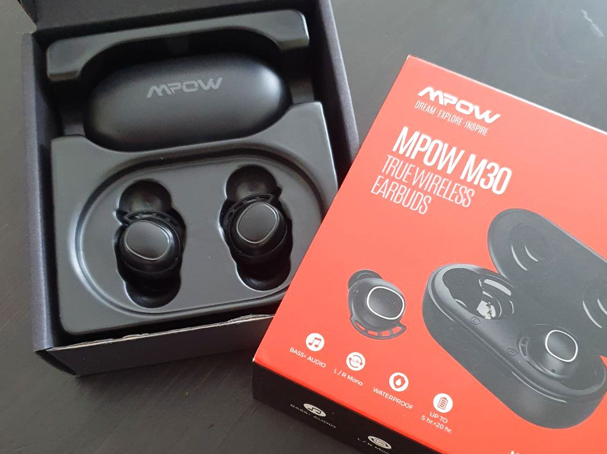 pair of black wireless bluetooth earbuds and charging case next to their box