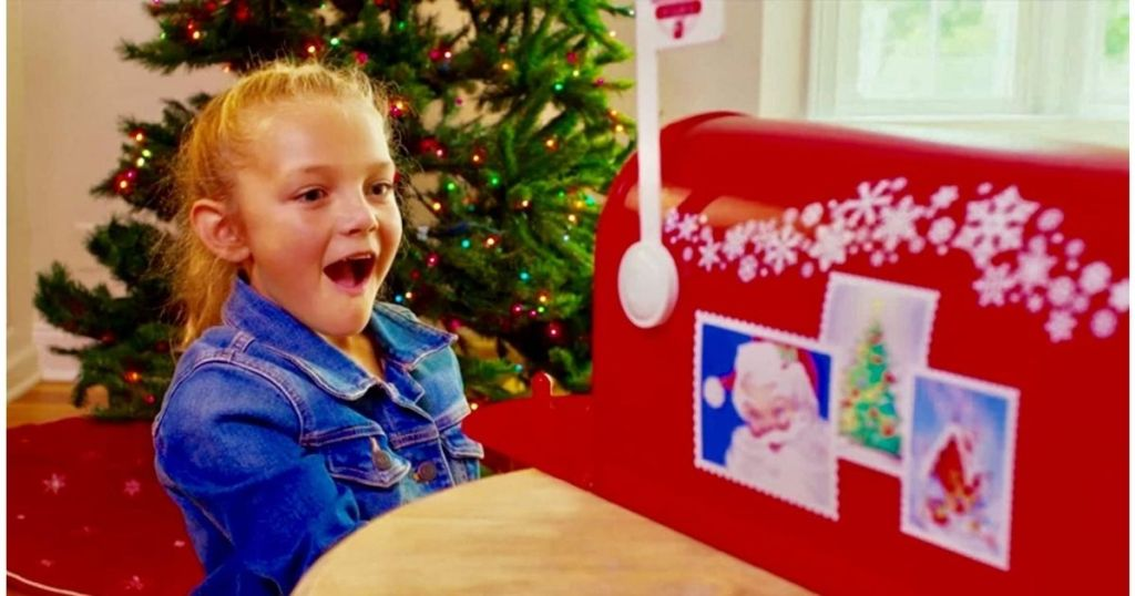 little girl looking into red Santa Mailbox with amazed look on her face