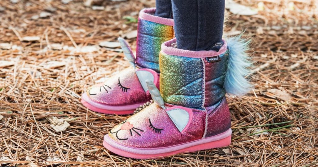 girl standing in bark wearing pink rainbow unicorn boots