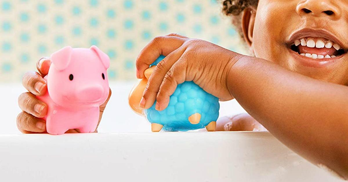 Young girl in tub holding farm animal bath toys