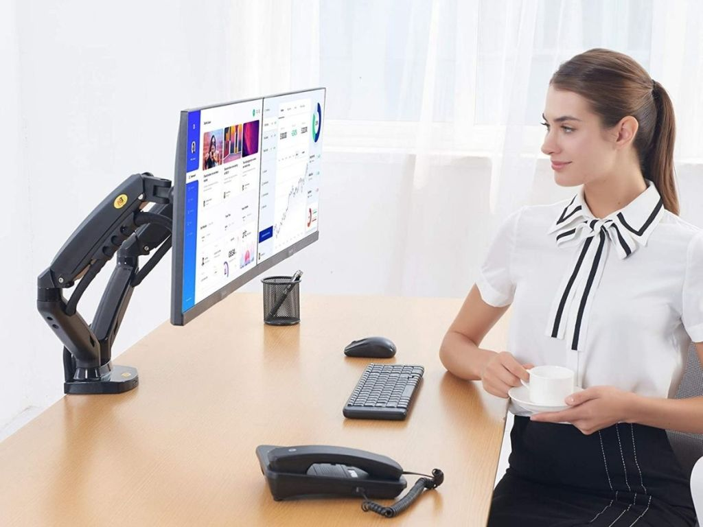 woman sitting at desk holding coffee cup looking at her computer monitor