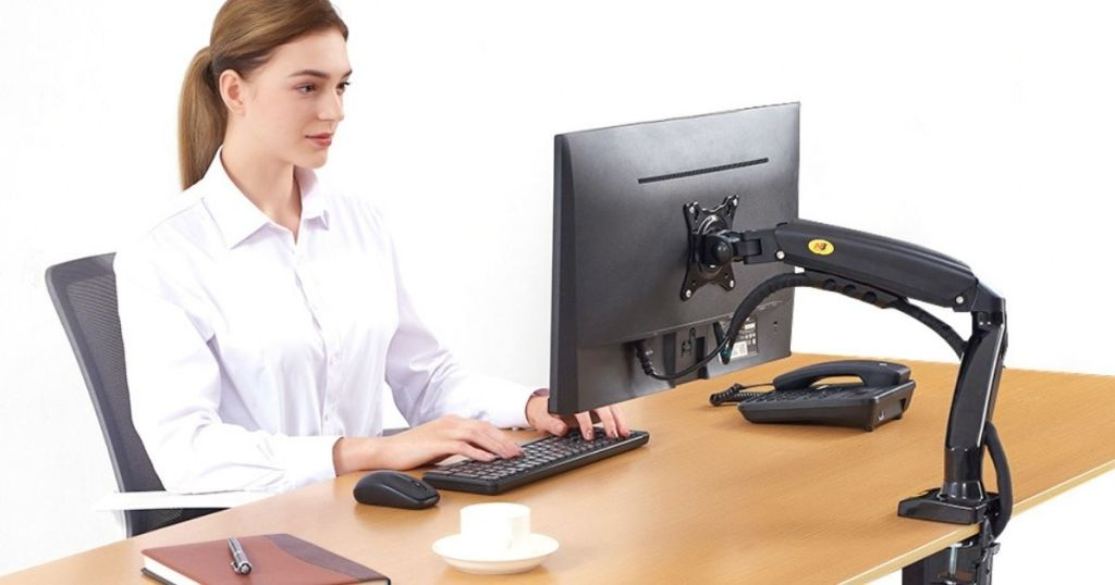 woman sitting at desk using keyboard and looking at compuer