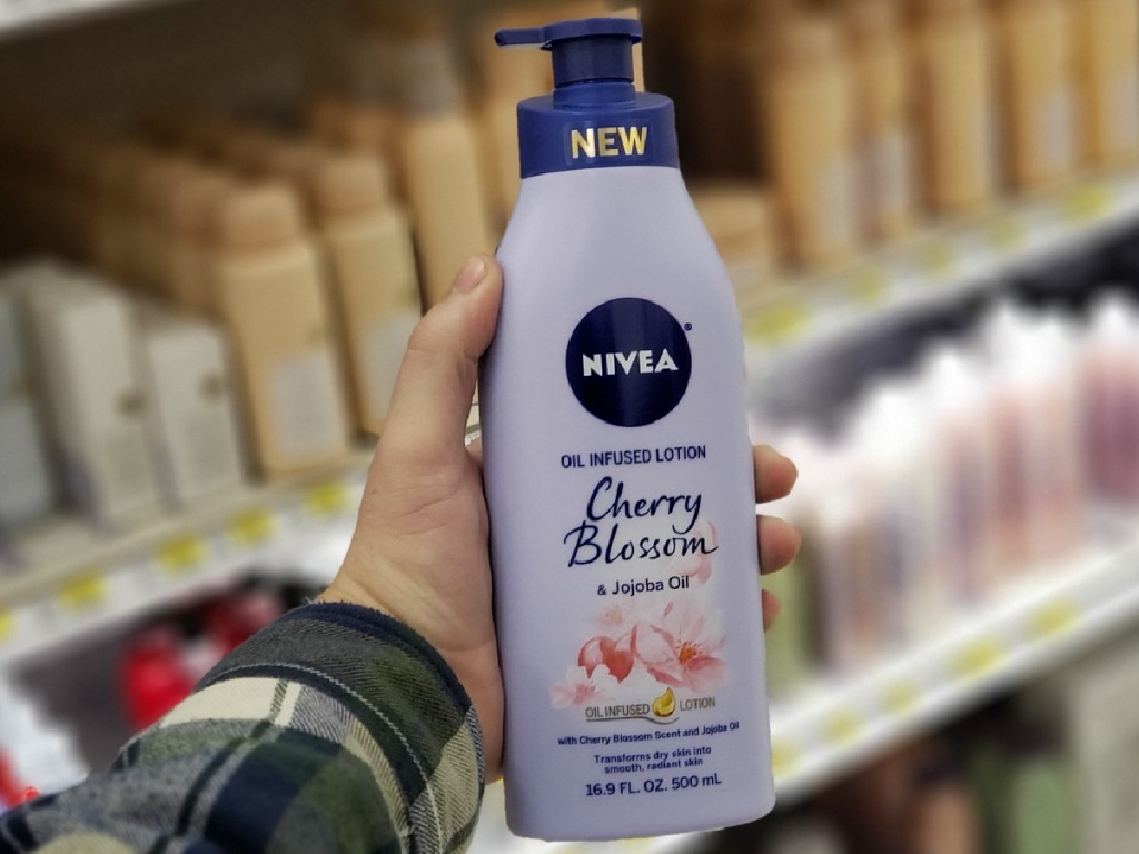 hand holding bottle of lotion in store