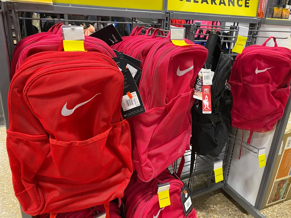 red, pink, and black mesh backpacks hanging in store