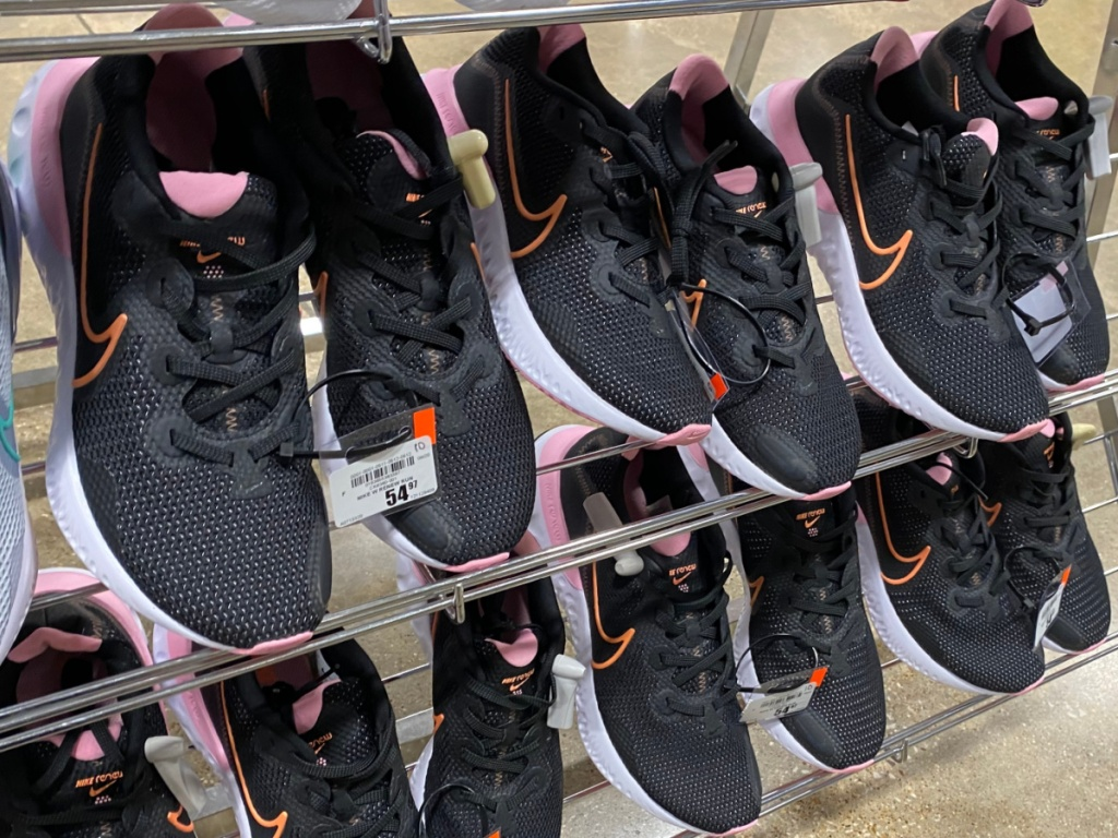 black, white, orange, and pink women's running shoes on shoe rack display in store