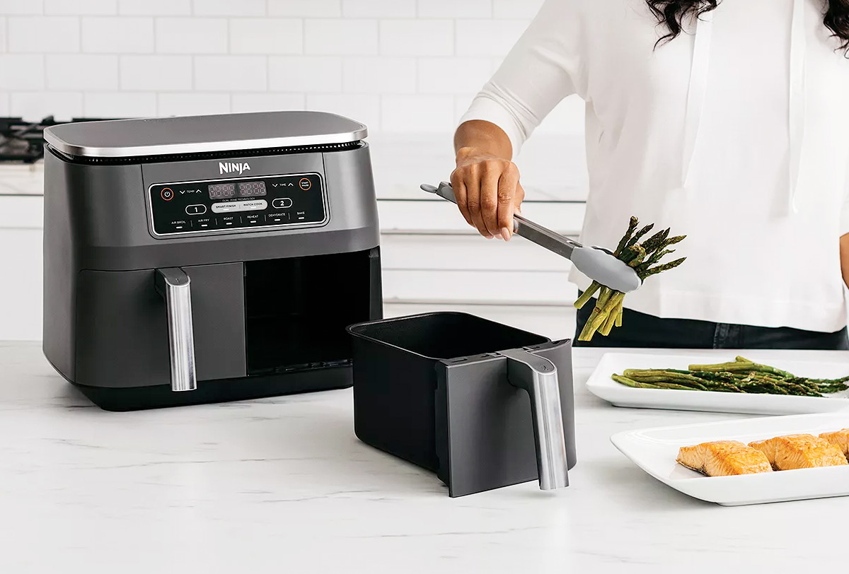 woman using a Ninja Foodi air fryer with two frying baskets to cook asparagus and salmon