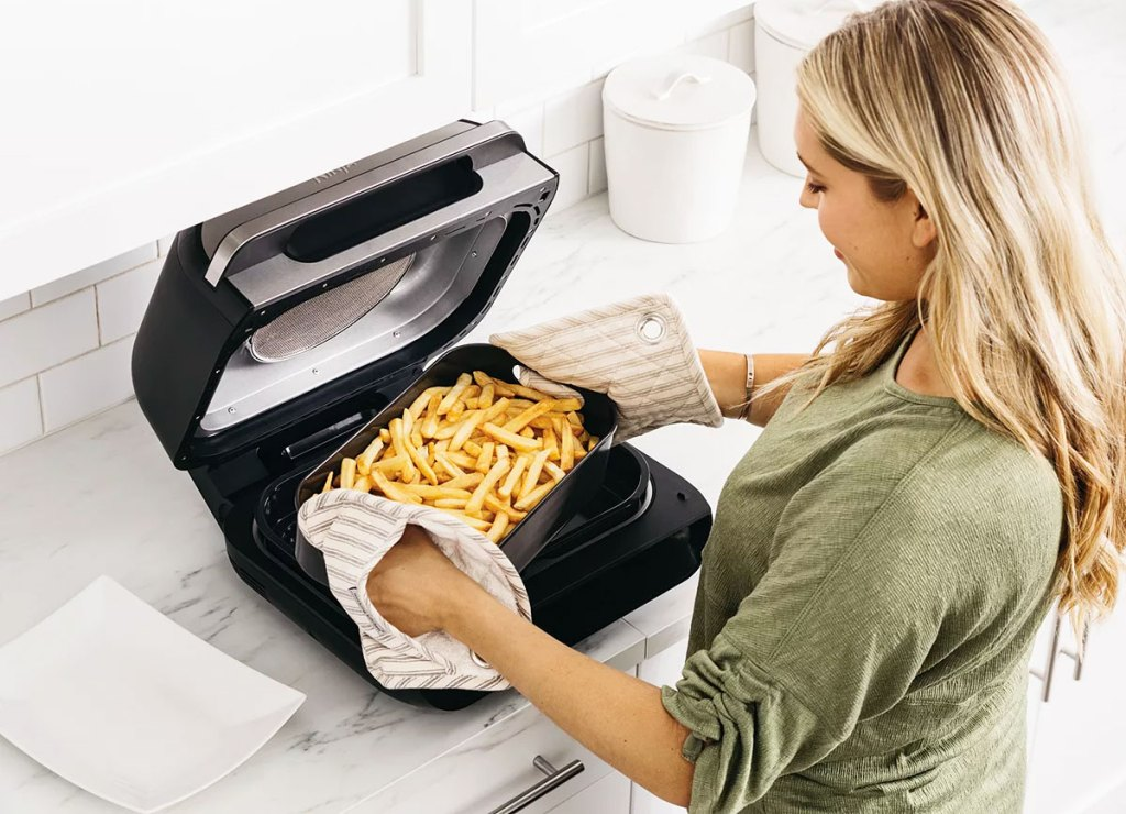woman removing a basket of french fries from Ninja Foodi grill