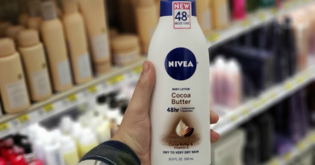 Man's hand holding Nivea Cocoa Butter Lotion