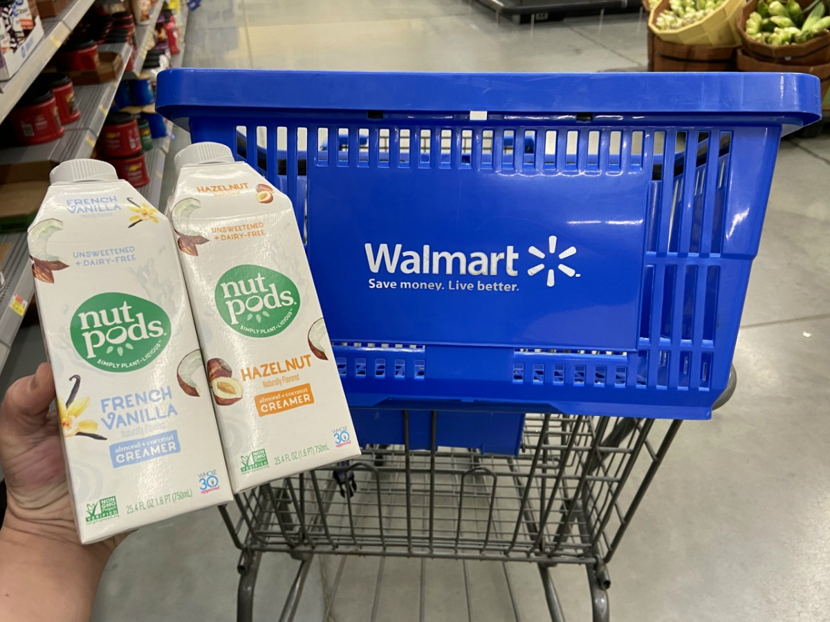 Hand holding two containers of nutpods creamer near a Walmart shopping basket