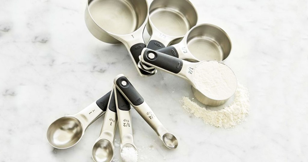 matching stainless steel and black measuring spoons and cups on marble counter with flour