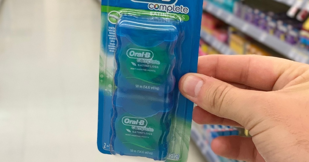 Hand holding oral-b satin dental floss 2-pack inside a store