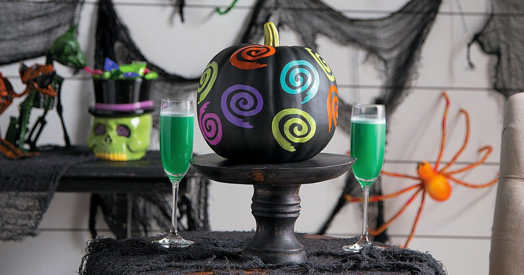 black pumpkin with neon colored swirl design on black pedestal with green drinks and halloween decor in background