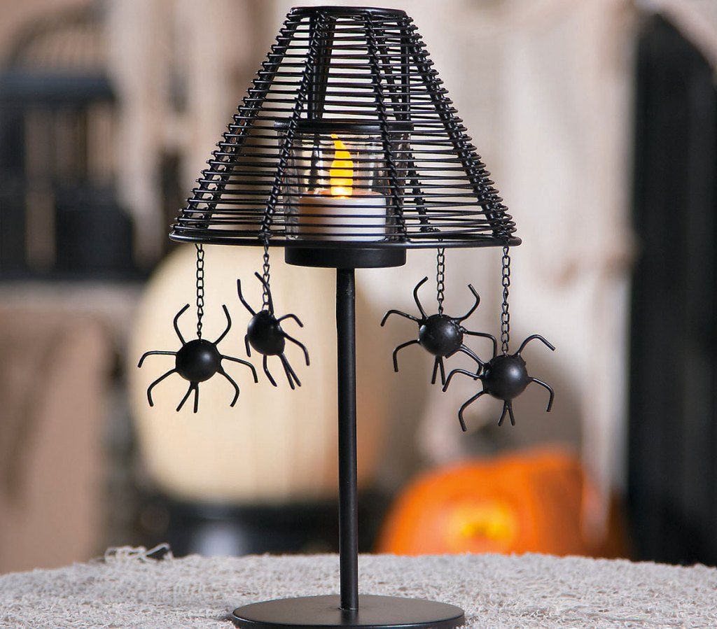 black lamp shaped votive candle holder with four spiders hanging off the edges