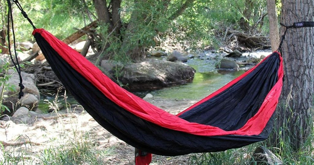 black and red hammock tied up to trees in woods