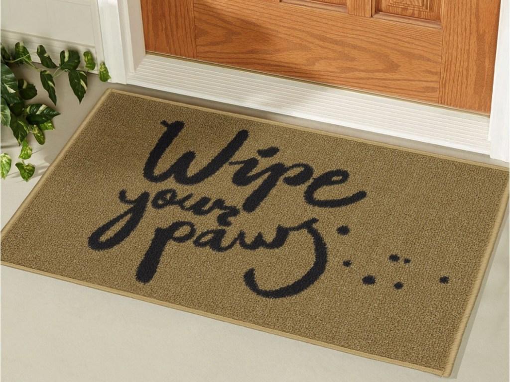 """beige """"wipe your paws"""" doormat in front of door"""