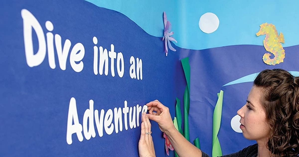 woman putting letters on a bulletin board