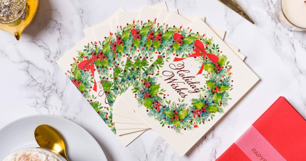 Christmas cards that read holiday wishes surrounded. by a christmas wreath