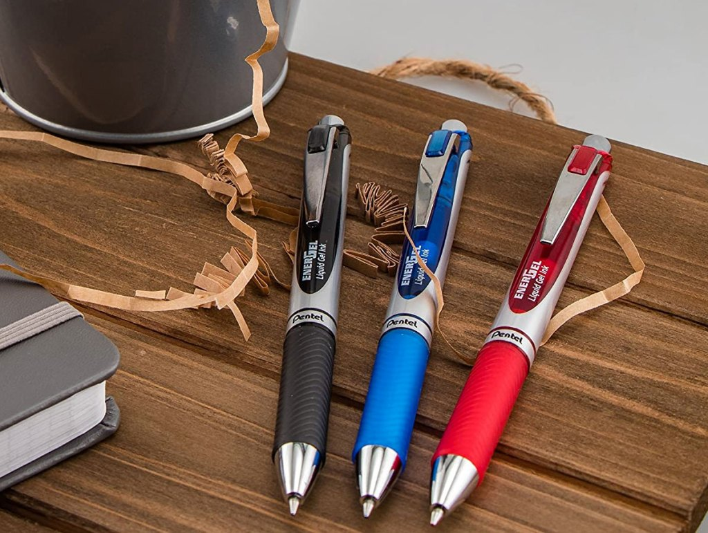 three pentel pens on wood table in black, blue, and red ink colors