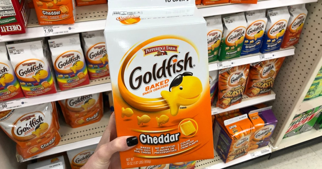 woman's hand holding large carton of cheddar goldfish crackers in store