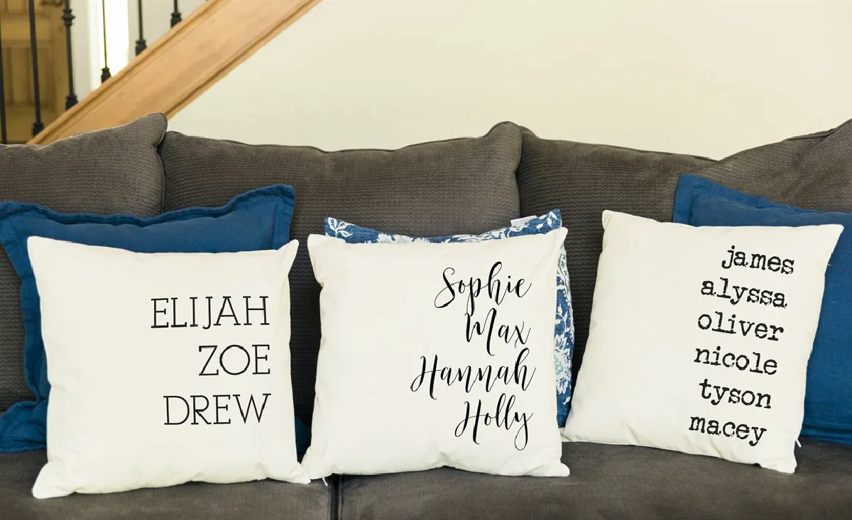 three blue pillows and three white pillows with printed names on couch