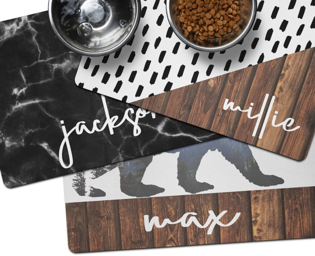 three personalized pet mats with bowls of food and water on top