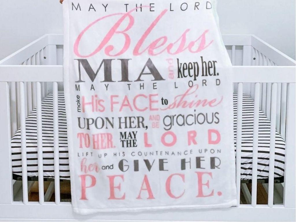"personalized ""bless"" blanket draped across white crib"