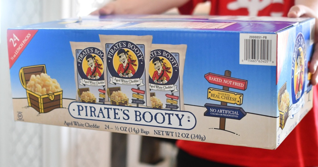 person holding a large 24-count box of pirates booty snacks