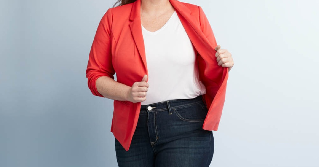 woman in white tee, jeans, and red blazer