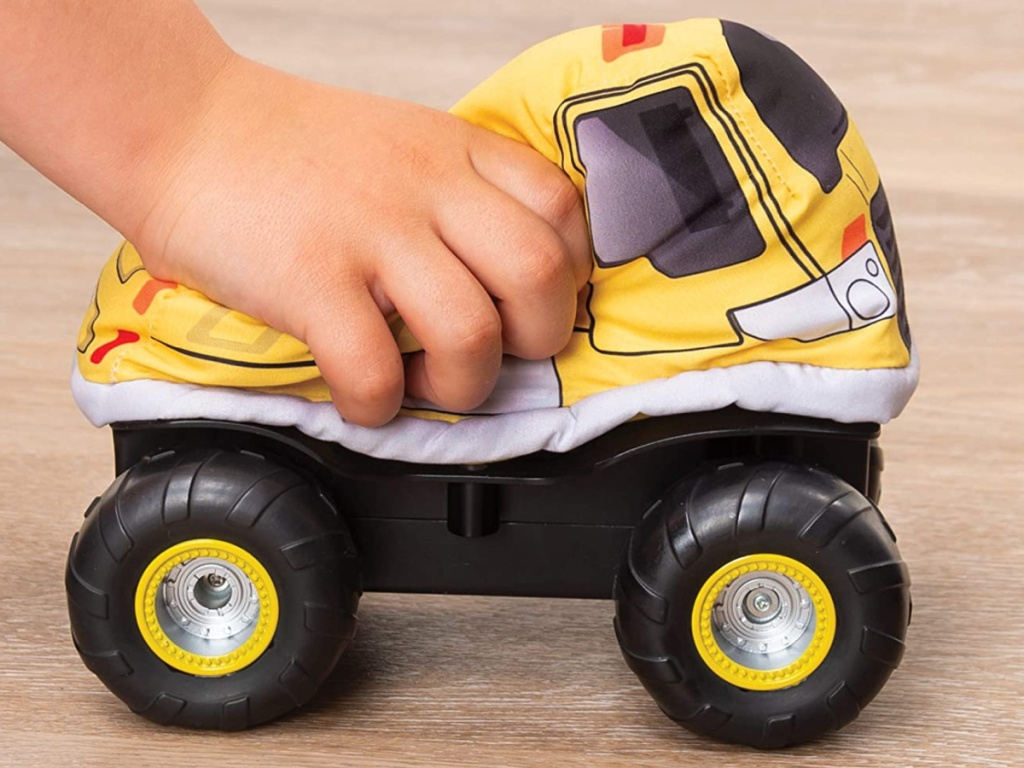 child playing with plush remote control dump truck on hardwood floor