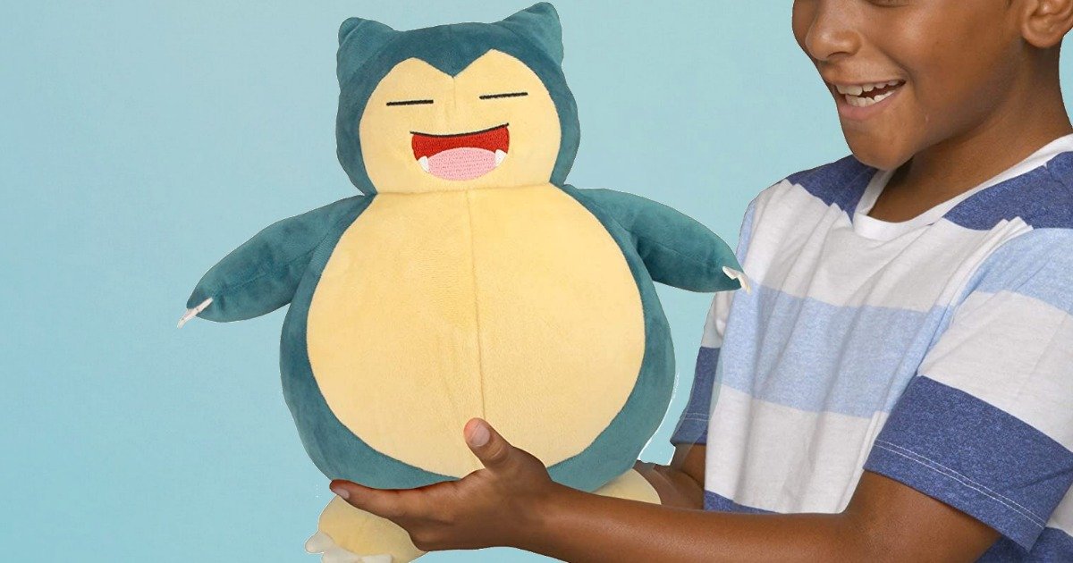 Large Pokemon plush toy being held by a young boy