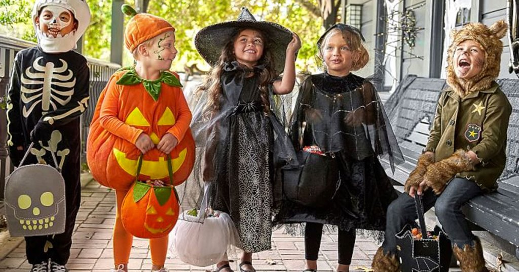 group of kids standing outside dressed in halloween costumes and holding treat bags