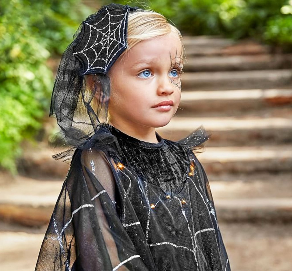 girl with blonde hair dressed in black dress with silver spider web details and spider web accessory in her hair