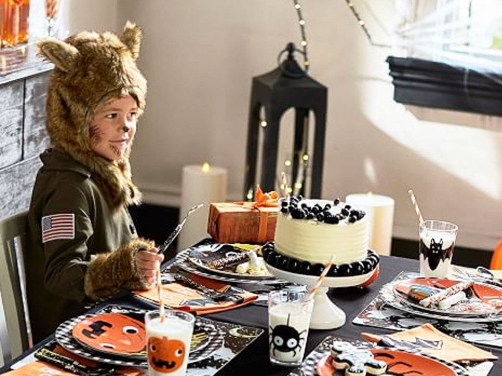 boy dressed in werewolf halloween costume sitting at a table with halloween party supplies
