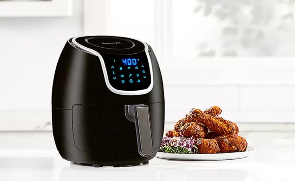 black air fryer with blue digital touch screen on white countertop with plate of chicken wings