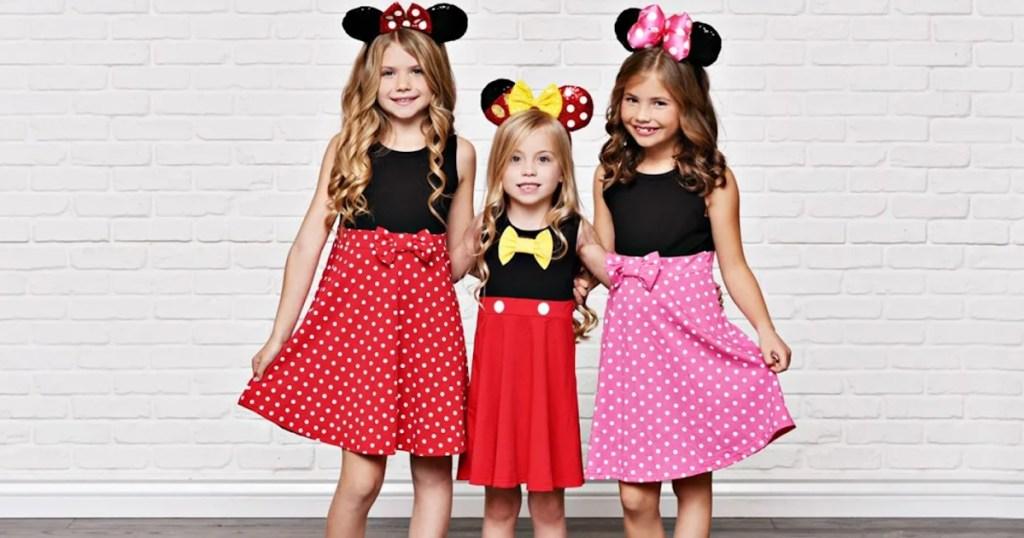 girls wearing disney dresses and ears