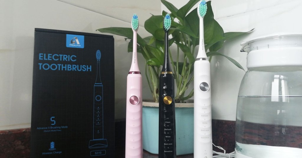pink, black, and white electric toothbrushes on counter near a black electric toothbrush box